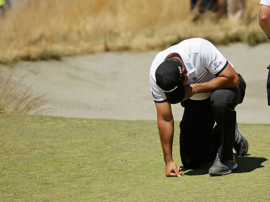 Jason Day kneels while waiting to putt on the ninth hole after having collapsed earlier in the fairway during the second round.