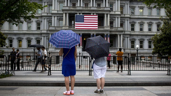 Two women look at a US National flag on the side of
