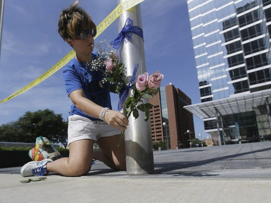 Noelle Hendrix places flowers near the scene of a shooting in downtown Dallas, Friday, July 8, 2016. Someone opened fire on police officers in the heart of Dallas during protests over two recent fatal police shootings of black men.
