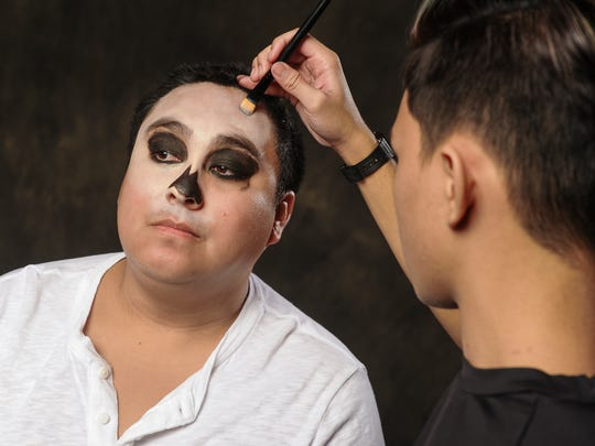 After using black gel eyeliner to shade in the eye sockets and the appearance of a nasal cavity, freelance makeup artist Clay Josh Aflleje now uses a cream consealer to simulate a bone color on the face of Pacific Daily News reporter Shawn Raymund during a Halloween transformation into a skeleton on Thursday, Oct. 13.