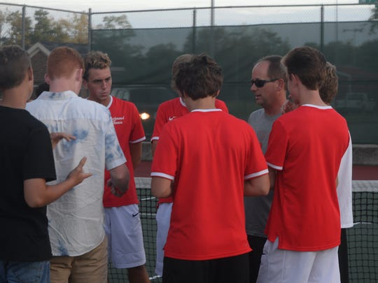 Richmond head coach Randy Hollingsworth talks to his players after the Red Devils defeated Batesville 4-1 for a fourth straight IHSAA boys tennis regional championship Wednesday, Oct. 4, 2017.