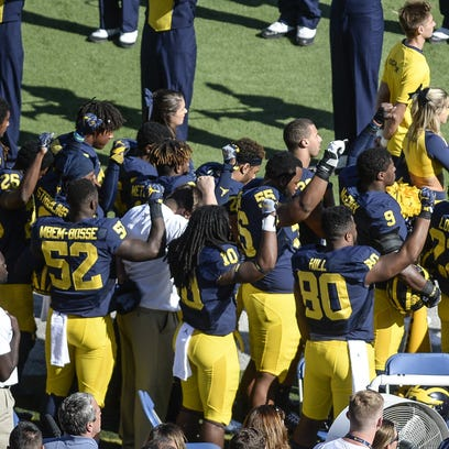 Some Michigan players raise their fists during the