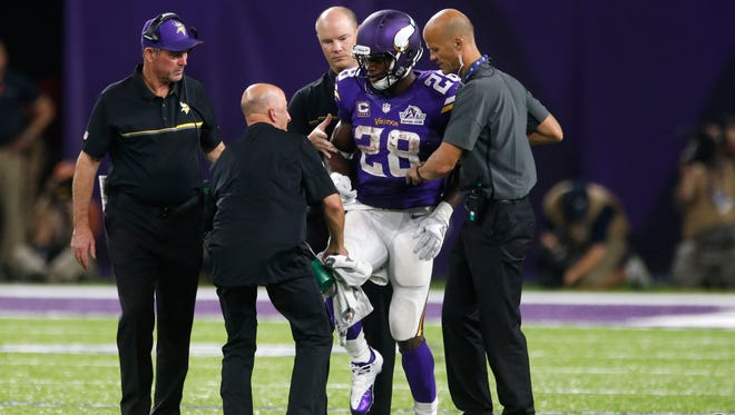Minnesota Vikings running back Adrian Peterson (28) is helped off the field after getting injured during the second half of an NFL football game against the Green Bay Packers Sunday, Sept. 18, 2016, in Minneapolis.
