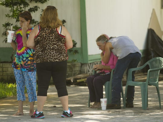 Tammy Rawson, right, is comforted at the scene of a death investigation in San Carlos Park. Rawson is the mother of one of the deceased.