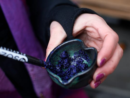 The Rev. Jen Hibben, pastor at Thrive United Methodist Church, mixes glitter, ashes and oils together Wednesday, March 1, 2017 before members of Ashes for All offer up glitter ashes for Ash Wednesday outside of Blazing Saddle in the East Village of Des Moines.