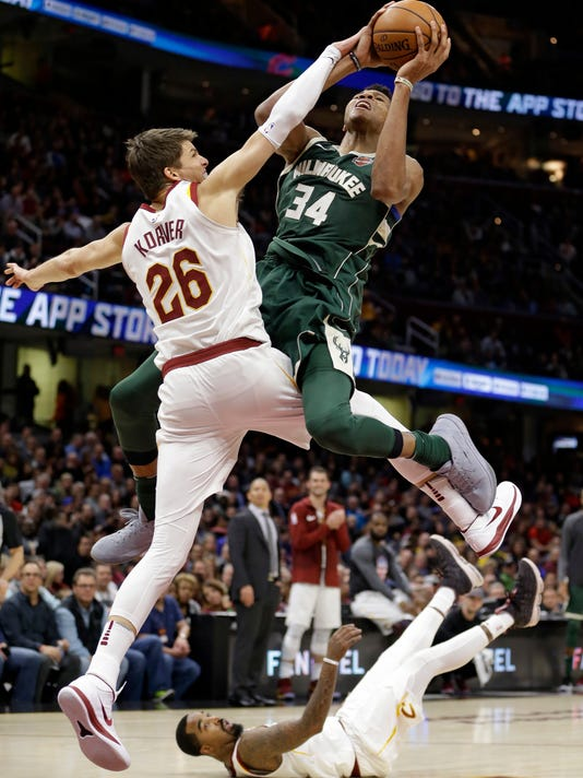 Milwaukee Bucks' Giannis Antetokounmpo (34), from Greece, drives to the basket against Cleveland Cavaliers' Kyle Korver (26) in the second half of an NBA basketball game, Tuesday, Nov. 7, 2017, in Cleveland. JR Smith watches from the floor. The Cavaliers won 124-119. (AP Photo/Tony Dejak)
