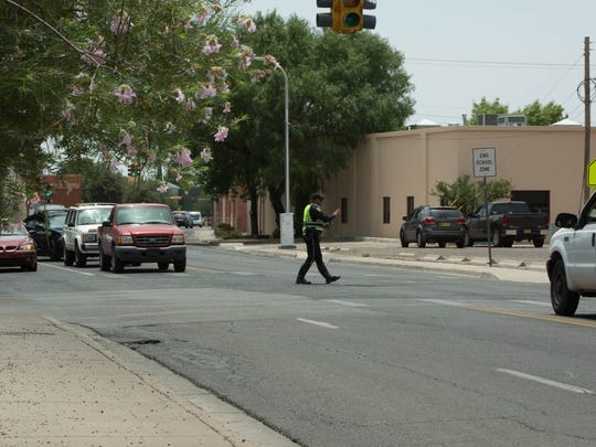 "An off-duty Las Cruces police officer directs traffic at the intersection of Las Cruces Avenue and Alameda Boulevard on Tuesday, July 24, 2018, while the Clint Eastwood movie ""The Mule"" filmed scenes nearby."