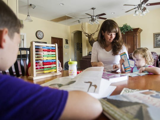 Gina Ray's three children work on school work in their home on Wednesday, July 29, 2015. Ray is protesting the new Arizona state testing and has decided to keep her children out of school and give homeschooling a try.