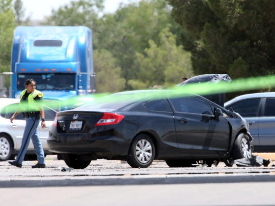 An El Paso police officer walks past one of the vehicles involved in a fatal traffic accident at Pan American Drive and South Americas Avenue on Thursday afternoon.