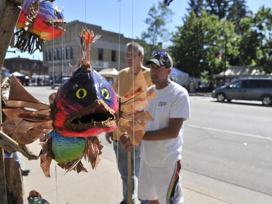 Vendor Mark Feja talks with a customer about his coconut-carved