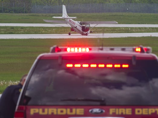 Emergency crews wait after a single engine plane crashed on a runway at Purdue University Airport Saturday, May 17, 2014, in West Lafayette. The two occupants of the plane were not injured in the accident.