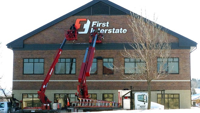Workers install a sign for First Interstate Bank in early 2015 on the building where it leases space for its mortgage office.