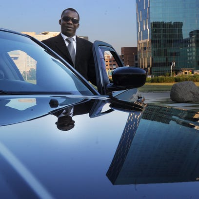 Uber driver Edward Ogundana, Indianapolis, stands by his car as he delivers passengers to a party in June 2013. App-based Uber and Lyft have reached agreements to serve travelers at Indianapolis International Airport in time for the Final Four.