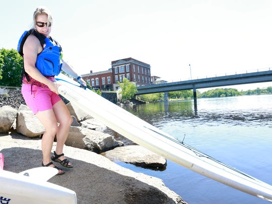 Kim Kinsey handles a paddleboard on the Wisconsin River