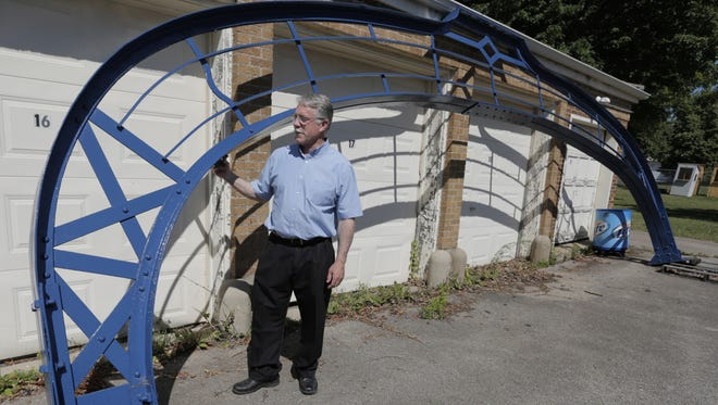 """Winnebago County Parks Director and Expo Manager Rob Way looks over the metal work of the arch that once stood at the old fairgrounds entrance on Murdock Avenue. The """"Raise the Arch"""" campaign looks to raise about $3,000 at this year's Winnebago County Fair to finish restoring the 90-year-old steel archway later this year."""