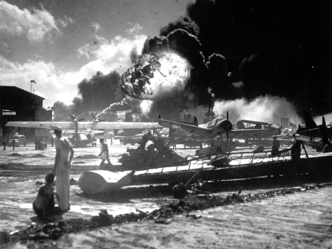 In this Dec. 7, 1941 photo sailors stand among wrecked