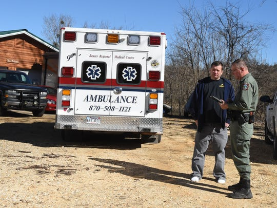 Arkansas Game and Fish Commission officer Lyndle Crownover, right, speaks with one of three men rescued from the White River late Friday morning. The men were fishing when their boat submerged after striking a pylon of the Sheid Bridge.