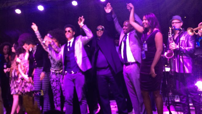 Stevie Wonder, middle, made a surprise appearance at the purple-lit Prince tribute concert in L.A. to sing 'Purple Rain.'