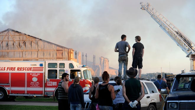Bystanders watch as emergency crews respond to a fire off I-29 near Tea, S.D., Tuesday, Aug. 12, 2014.