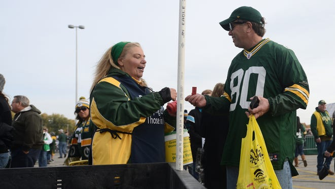 Kyle Bursaw/Press-Gazette Media Paul's Pantry volunteer Kim Bassett gives a raffle ticket to Tom Baeten of Sacramento for his food donation to the Packers Women's Association annual food drive for Paul's Pantry before the game Sunday against the Carolina Panthers at Lambeau Field in Green Bay. Paul's Pantry volunteer Kim Bassett gives a raffle ticket to Tom Baeten of Sacramento for his food donation to the Packers Women's Assocation Annual Food Drive in association with Paul's Pantry before the game against the Carolina Panthers at Lambeau Field in Green Bay, Wis. on Sunday, Oct. 19, 2014. Kyle Bursaw / Press-Gazette Media / @kbursaw