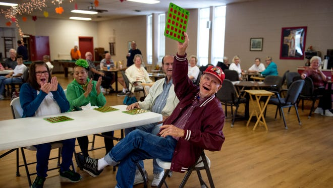 Gilmer Thomas raises his board after winning a bronze medal in the Bingo competition during the Henderson Senior Games at The Gathering Place on Thursday. This year is the first time the Henderson Senior Games has held a Bingo competition.