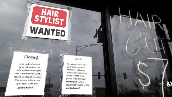 FILE - In this April 30 ,2020 file photo, a barber shop shows closed and hiring sign during the COVID-19 in Chicago. On Thursday, Aug. 27, just over 1 million Americans applied for unemployment benefits last week, a sign that the coronavirus outbreak continues to threaten jobs even as the housing market, auto sales and other segments of the economy rebound from a springtime collapse.