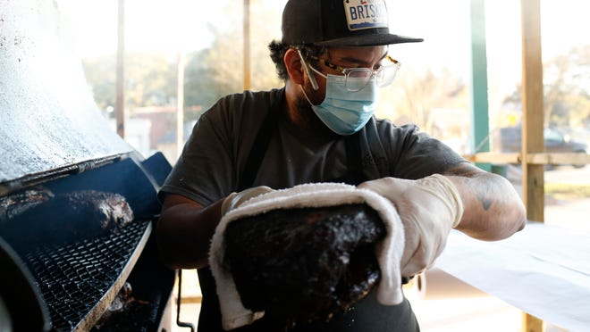 Alejandro Tamez removes the brisket after several hours to wrap it late in the afternoon on Wednesday, Nov. 25, 2020.