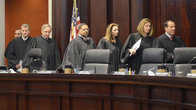 The justices of the Michigan Supreme Court enter their courtroom on January 13. The justices are, from left to right, Richard Bernstein, Bridget Mary McCormack, Mary Beth Kelly, Chief Justice Robert Young., Jr., Stephen Markman, Brian Zahra and David Viviano. With two weeks left in the court's term, state workers are still waiting for rulings on their fates.