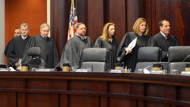 The justices of the Michigan Supreme Court walk into the courtroom on Jan. 13 to hear arguments on whether the Legislature stepped on the authority of the Michigan Civil Service Commission with a 2011 requiring thousands of state employees to pay more to retain full pension benefits. If the court rules for the employees, it could take more than $120 million from the State Employee Retirement System. The justices are, from left to right, Richard Bernstein, Bridget Mary McCormack, Mary Beth Kelly, Chief Justice Robert Young., Jr., Stephen Markman, Brian Zahra and David Viviano.