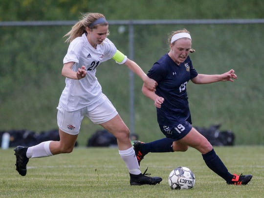 Sheboygan North's McKayla Kertscher (19) battles Arrowhead's Emma Mueller for the ball during a WIAA Division 1 sectional championship match in Germantown.