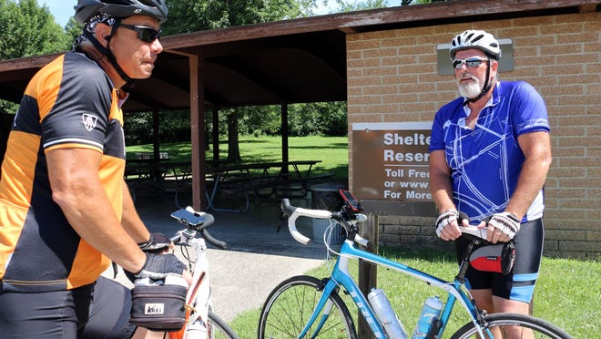 Don Labate, left, and Scott Carroll, go biking on Wednesday, July 29, 2015, along the Neal Smith Trail along Saylorville Lake and Big Creek State Park. Carroll continues to recover after he was hit by a car on his bike on July 10, 2014.