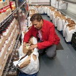 Millie Jeter, an employee of Lunch Break, checks food baskets waiting for distribution.