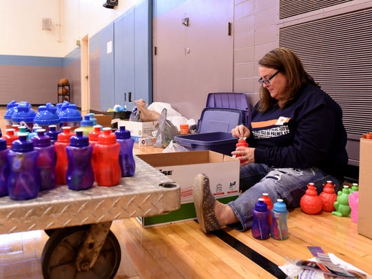 Melanie Timmerman fills water bottles with candy while preparing items to be packed by volunteers for Operation Christmas Child on Friday, Nov. 4 at the Licking County Family YMCA. The collected items were boxed to be sent to children around the world for Christmas. Items included toys, clothes, and personal care items.