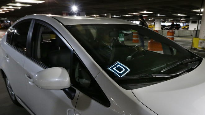 A driver for Uber Technologies Inc. arrives March 31 at an authorized customer pickup area at Seattle-Tacoma International Airport in Seattle.
