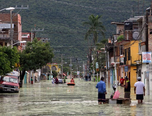 Heavy rain flooded the main street of Tixtla on Sept. 19 in Guerrero, Mexico. Tropical storms Ingrid and Manuel triggered massive floods and landslides, destroying roads, homes and businesses.