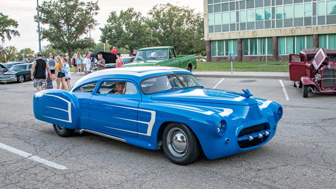A blue vintage car, which won best of show during last year's Cruisin' the Capitol car show, drives through downtown Toepka.