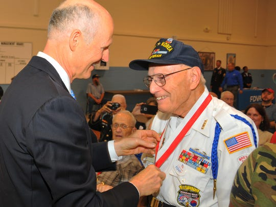 Then Gov. Scott gives George Rosenfield of Suntree, a WWII and Korean war vet, his medal. Rosenfield is a member of the Jewish War Veterans of America.