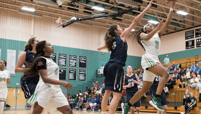 Fort Myers High School's Destanni Hendson puts the ball up past Dana Bandurick of Newtown (Pa.)-Council Rock North in the first round the Naples Holiday Shootout at Gulf Coast High School on Thursday, Dec. 28, 2017.