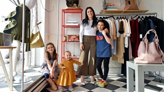 """Hilary Arthur, second from right, stands for a portrait with her daughters, from left, Eleanor, 7; Reed, 15 months; and Violet, 9, in her North Beaver Street store Arthur & Daughters Friday, March 23, 2018, in York. """"I think something like this really works in a place like York,"""" Arthur said of having her daughters in the store with her. """"People are very community-oriented; they're very family-oriented. They don't come here expecting what you get at the mall. I think that's special and that's what makes us unique."""" A handful of downtown York business owners bring their babies or kids to work, citing daycare costs or the flexibility they enjoy as their own bosses."""