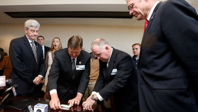 Incumbent Rep. Bo Eaton, D-Taylorsville, center left,  and Republican challenger Mark Tullos, center right, open and display the contents of silver-plated business card boxes in the governor's office near the state Capitol Nov. 20 in Jackson as Gov. Phil Bryant, left, and Secretary of State Delbert Hosemann, right, look on. Eaton picked the one with the longer, 3-inch green straw, giving him the victory and blocking the GOP from having a supermajority in the House. Both candidates were deadlocked following the Nov. 3 election.