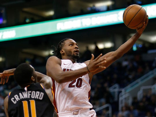 Miami Heat forward Justise Winslow (20) drives by Phoenix Suns guard Jamal Crawford during the first half during an NBA basketball game Friday, Dec. 7, 2018, in Phoenix. (AP Photo/Rick Scuteri)