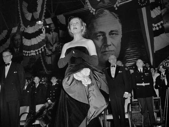 Carole Lombard leads the crowd in song during a war