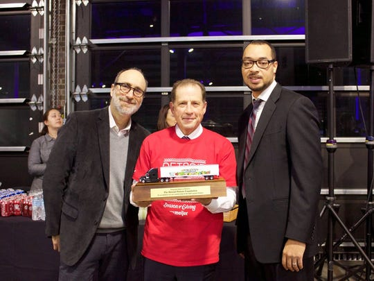 "Palace Sports & Entertainment Vice Chairman Arn Tellem accepts Forgotten Harvest's highest honor, a ""Harvey"" award, from Forgotten Harvest Chairman Hannan Lis (left) and CEO Kirk Mayes."