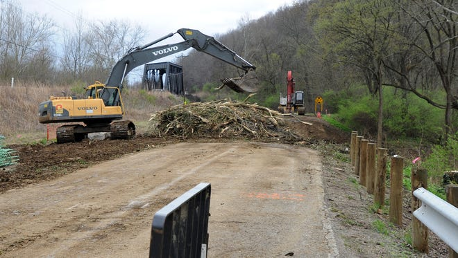 A construction crew works Monday on the bridge on Three Locks Road. The mild winter has helped the construction being done on Ross County roads and bridges this year.