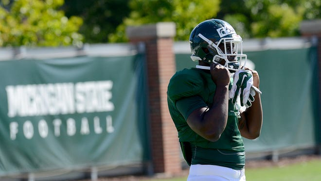 Freshman running back LJ Scott straps on his helmet as he gets ready for drills Wednesday during practice for the Spartan football team.