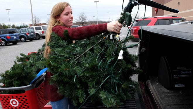 Heidi DalPezzo, 20 of West Manchester Township, loads an artificial tree into the bed of her boyfriend Gary Polomski's pickup truck bought at after-Christmas sales at Target, Saturday Dec. 26, 2015.(John A. Pavoncello - The York Dispatch)
