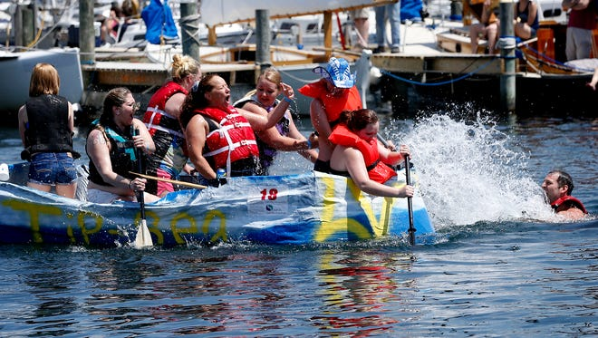 The Tip Sea crew gets splashed by fellow competitors Saturday during the Nearly Famous Cardboard Boat Regatta in Watkins Glen's Seneca Lake harbor.