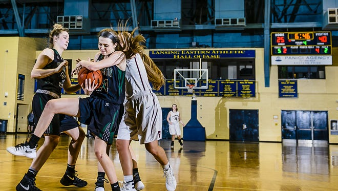 Kenzie Lewis, foreground, of Williamston grabs a defensive rebound in front of Lauren Russell, right, of Portland early in the 4th quarter of their Class B regional championship game Thursday March 9, 2017 at Don Johnson Fieldhouse in Lansing.
