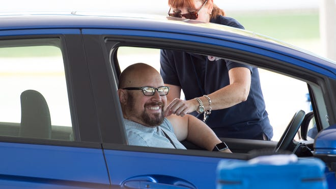 Michael Sandler of Wilmington smiles after receiving a flu shot from Yvonne Nelson, BSN, RN at the Division of Public Health's drive-thru flu vaccination clinic at the DelDOT Administration Building in Dover.