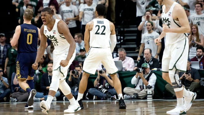 From left, Michigan State's Xavier Tillman, Miles Bridges and Ben Carter celebrate after a Bridges dunk during the second half on Thursday, Nov. 30, 2017, at the Breslin Center. The Spartans beat Notre Dame 81-63.